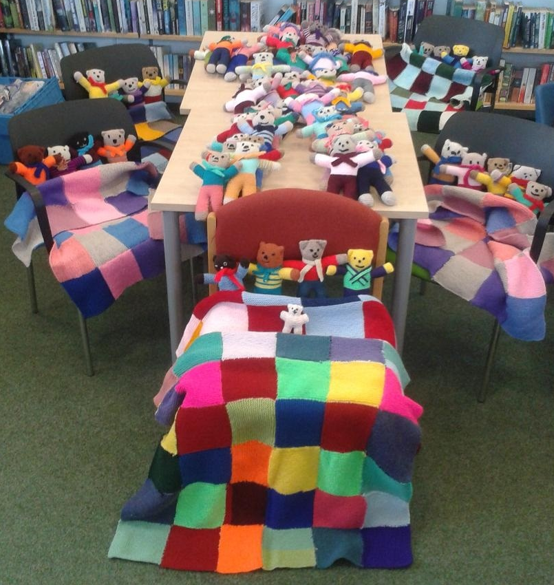 A display of handmade knittedquilts and small Teddy bears.