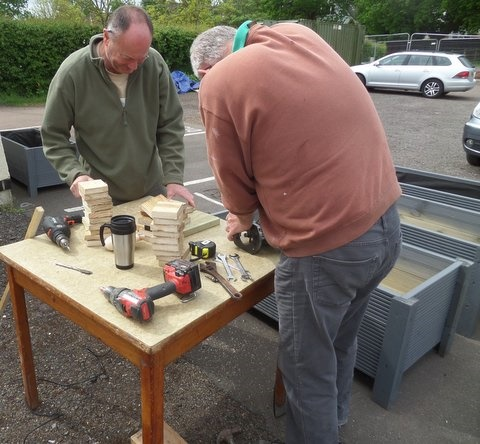 2 members of men in sheds manufacturing end caps to go on the corners of Planters