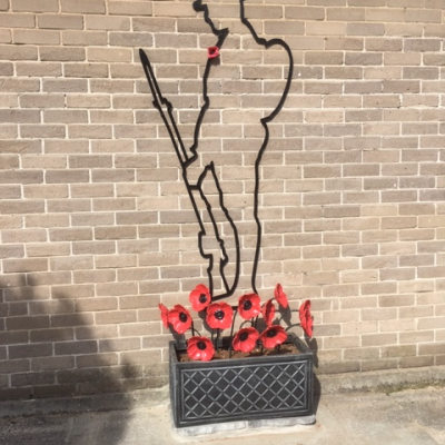 The Six foot There but NotThere Tommy Silhouette with a 12 red steel poppyies in a planter at the base of the Silhouette