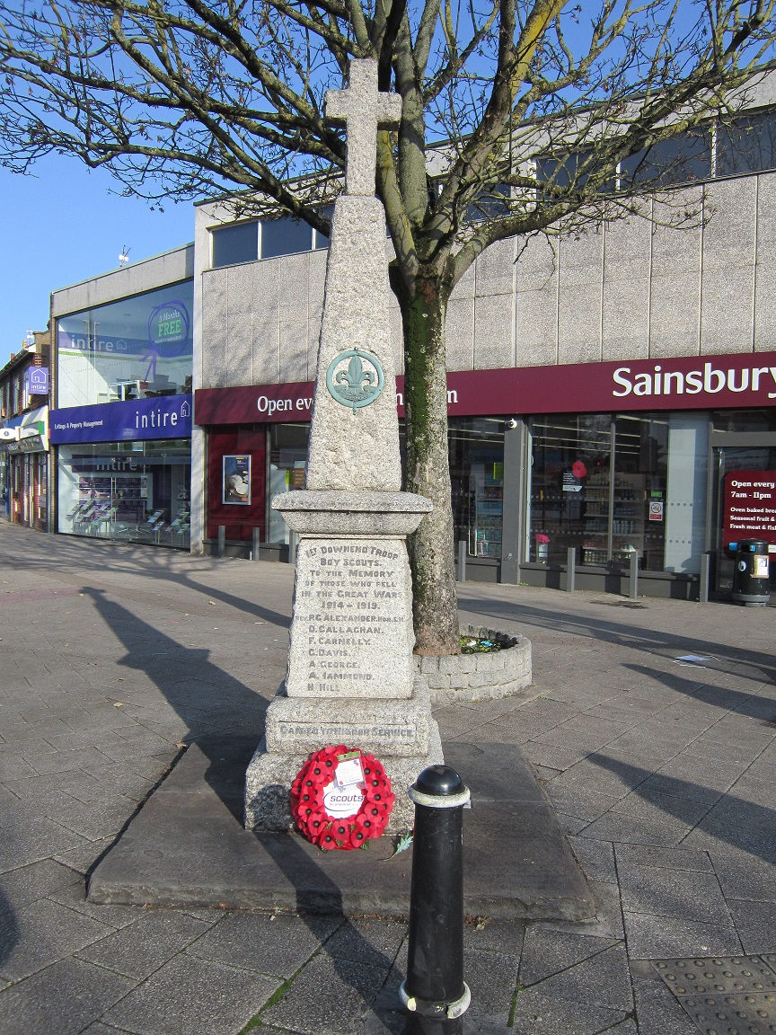 A colour photo of the Downend Scouts War Memorial with a poppy wreath at the foot of the memorial.